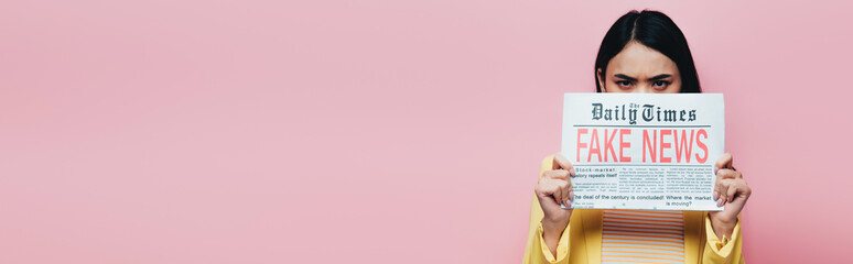 sad asian woman in yellow outfit holding newspaper with fake news isolated on pink, panoramic shot