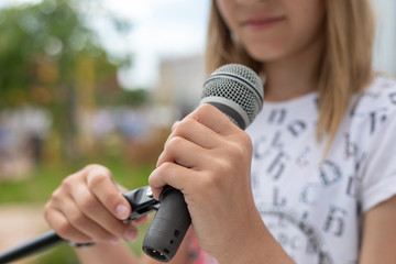 Young girl holding mic with two hands. Microphone and unrecognizable girl singer close up. Cropped image of female teen singer in park. Copyspace