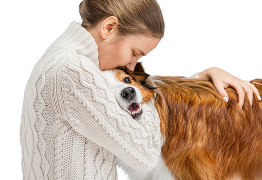 Young woman hugging a red dog. The background is isolated.