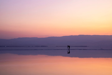 Photographer taking pictures of sunrise on the shore of the Dead Sea