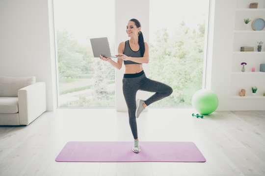 Full size photo of positive charming sportive girl work computer search films movies about doing sport exercise doing crossfit wellbeing warm-up standing on violet mat in studio house gym