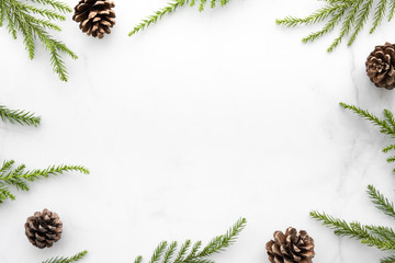 Obraz White marble table with Christmas decoration including pine branches and pine cones. Merry Christmas and happy new year concept. Top view with copy space, flat lay. - fototapety do salonu