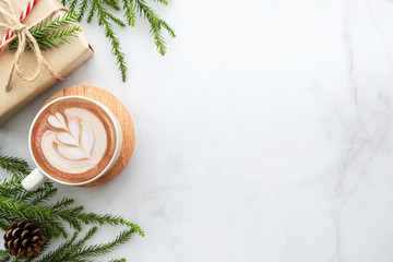 White marble table with cup of latte coffee and Christmas decoration with gift box. Christmas and new year celebration concept. Top view with copy space, flat lay.