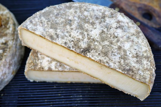 Fresh Tomme de Savoie cheese at a French farmers market