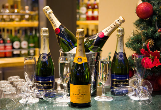 Luxury champagnes Veuve Clicquot, Moët & Chandon & Nicolas Feuillatte with flutes and a Christmas tree background. Christmas party. New Year's eve celebration