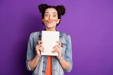 Portrait of funny funky girl do essay want rest relax make break pause fool grimace pencil between nose lips pouted plump hold note book wear trendy jeans clothes isolated violet color background