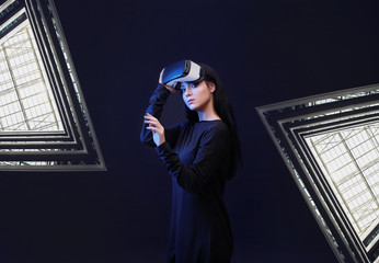 Wall Mural - Beautiful woman in VR helmet scrolling invisible screen while interacting with virtual reality under neon light. Girl in glasses of virtual reality. Augmented reality, game concept. Dark background.