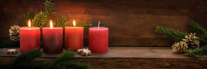 Third Advent, three of four red candles are lit with a flame, fir branches and Christmas decoration on dark rustic wood, wide panoramic format with copy space