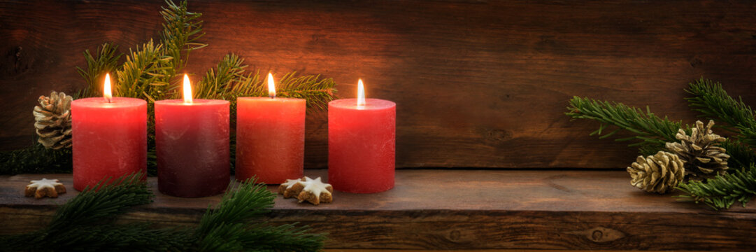 Fourth  Sunday in Advent, four burning red candles in a row, fir branches and Christmas decoration on dark rustic wood, wide panoramic format with copy space