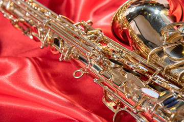 Beautiful macro photo of the details of a wind instrument of a golden alto saxophone on a red background