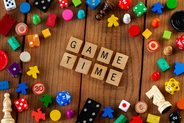"""""""Game Time"""" spelled out in wooden letter tiles. Surrounded by dice, cards, and other game pieces on a wooden background"""