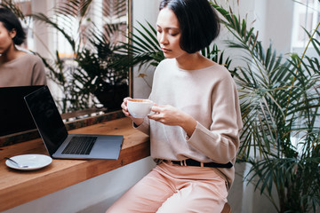 Young female asian adult drinking coffee and working on laptop