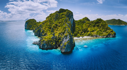Aerial drone panorama view of tropical paradise island. Karst limestone rocky mountains surrounds by blue ocean and coral reef