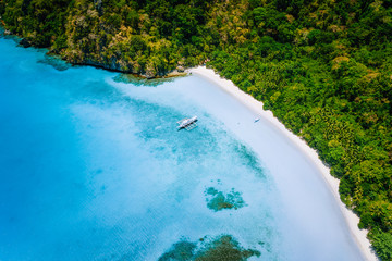Aerial top down view of boat moored at secluded white sand beach with coconut palm trees and...