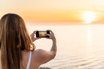 Young woman photographing a sunset on the beach with her mobile phone