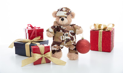 Cute teddy bear in soldier uniform and xmas presents isolated against white background