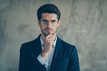 Close up photo of interested confident thoughtful man in eye wear touching his beard isolated grey...