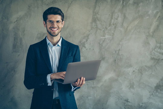 Photo of cheerful positive toothy beaming man holding laptop with hands smiling toothily cheerfully near empty space browsing isolated grey color background