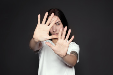 Young woman making stop gesture against dark background, focus on hand