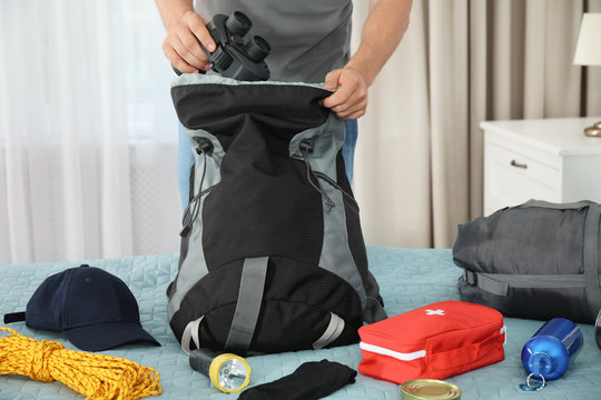 Man packing different camping equipment into backpack at home, closeup