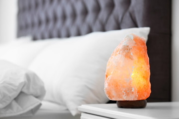 Himalayan salt lamp on table in bedroom. Space for text