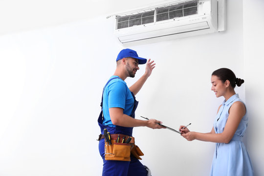 Professional technician speaking with woman about air conditioner indoors