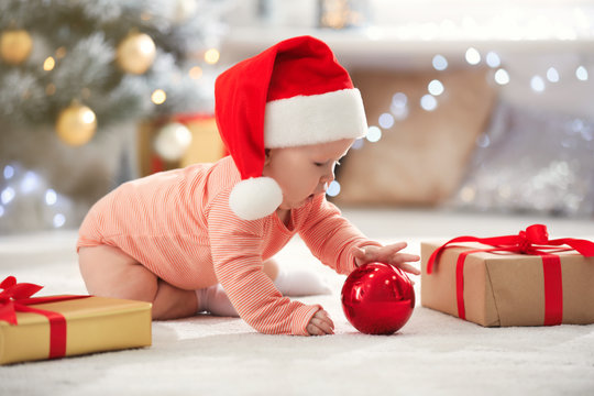 Little baby in Santa hat with Christmas decoration on floor at home