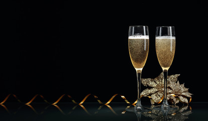 Two glasses of champagne ready to bring New Year on a black background.