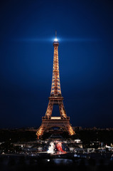 Eiffel Tower in night. Famous historical landmark on the quay of a river Seine. Romantic, tourist, architecture symbol. Toned. 24.04.2018 PARIS, FRANCE