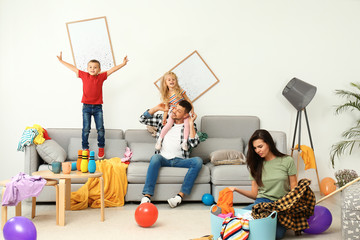 Frustrated mother trying to clean up mess while father playing with children in room