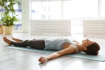 Young woman practicing corpse asana in yoga studio. Savasana pose Wall mural