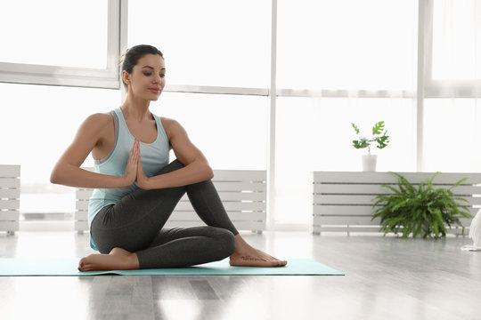 Young woman practicing lord of fishes asana in yoga studio. Matsyendrasana pose