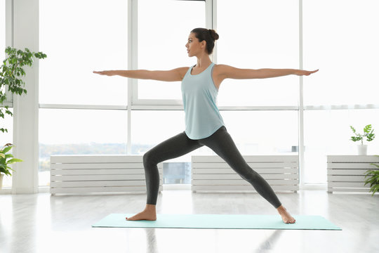 Young woman practicing warrior asana in yoga studio. Virabhadrasana pose