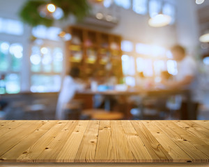 Empty brown old plank wooden board as mock up display shelf or table with blurred group of customer in coffee shop or bistro and soft bokeh from electric lamp and window lighting background.
