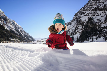 Child in snow has games and fun