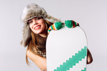 A young attractive woman is holding a snowboard