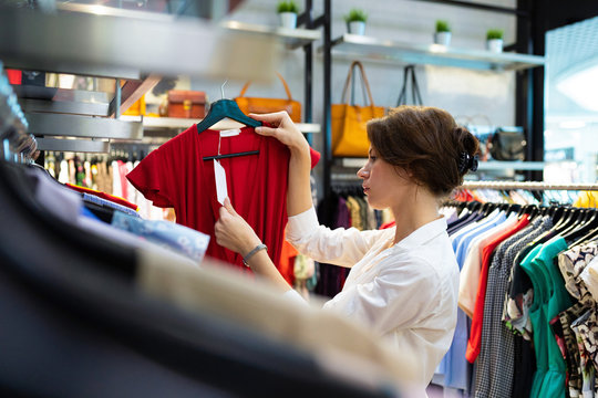 Attractive white woman looks at price tag at showroom