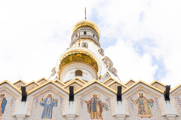 Bottom view of white church with gilt domes and images of saints