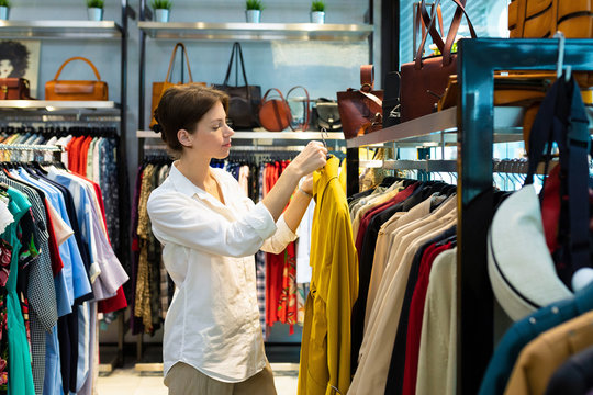 Young woman is choosing raincoat in clothing shop and holding one raincoat of mustard color
