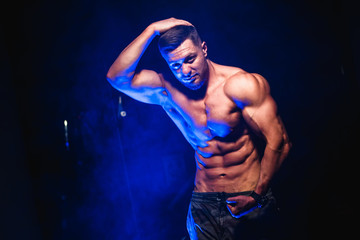 Bodybuilder showing belly and biceps muscles, personal fitness trainer. Strong man flexing muscles. Fitness model posing at camera. Black and blue light background.