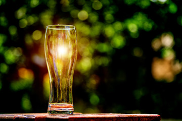 Close-up picture of an ampty beer glass on a brown wooden table. Sun shines through the glass. Blurred green nature background.