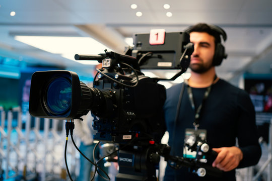 Professional cameraman with headphones with HD camcorder in live television