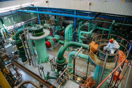 Worker repairs pipeline of water circulation in power plant