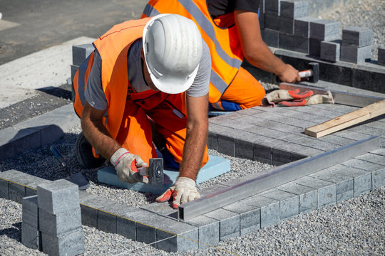 Construction workers laying paving bricks outdoor