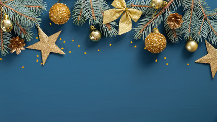 Christmas frame top border made of fir tree branches, golden decorative stars, balls over blue background. Flat lay, top view. Xmas banner mockup with copy space Fotobehang