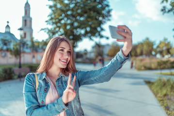 Beautiful girl student jeans holding mobile phone, takes pictures on smartphone, selfie, video call Internet application, summer city, fashionable and modern fashion lifestyle. Free space for text.
