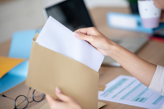 Close up of woman taking letter out of envelope