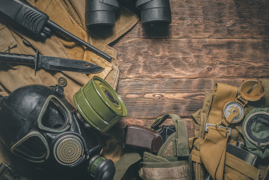 Post apocalypse soldier table concept background. Military equipment on old wooden background.