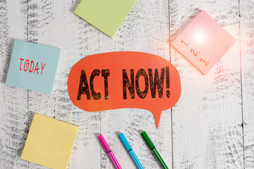 Text sign showing Act Now. Business photo text do not hesitate and start working or doing stuff right away Ballpoints pens blank colored speech bubble sticky notes wooden background