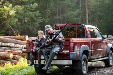 Door stickers Khaki Man at his truck with his son in the forest. Hunter teaches young boy how to use shotgun rifle.
